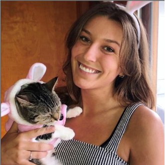 Jessica DeStefano holding her cat who is wearing a pink winter coat