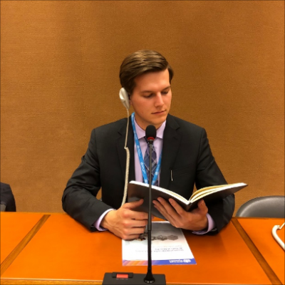 Hunter Kellogg siting at a conference room desk reading from a book into a microphone