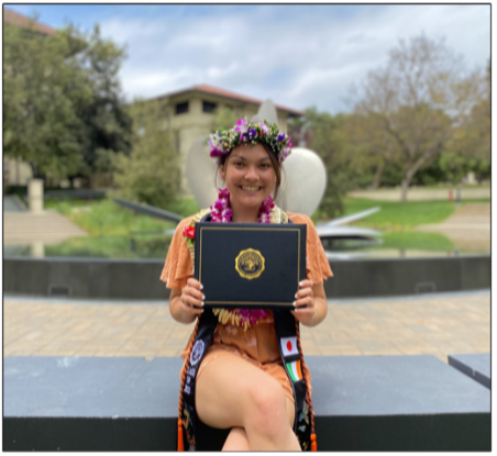 Mika O'Shea sitting on a bench holding her degree and posing for a photo
