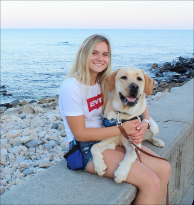 Rebecca Provesal sitting on the stone wall in narragansett ri holding her labrador retriever with the rocks and ocean behind her