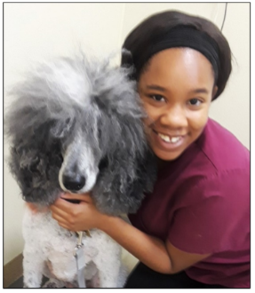 Dominique Shepherd posing with a grey and white dog who has a very fluffy and fury head